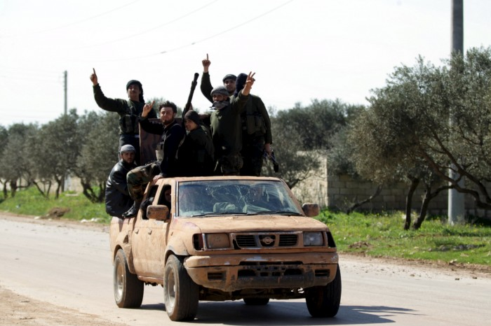 Ahrar al-Sham Islamic Movement rebel fighters ride on the back of a pick-up truck in the northwestern city of Idlib