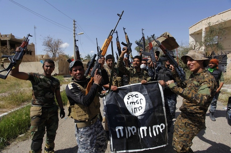Iraqi security forces and Shi'ite paramilitary fighters hold an Islamist State flag, which they pulled down in Tikrit