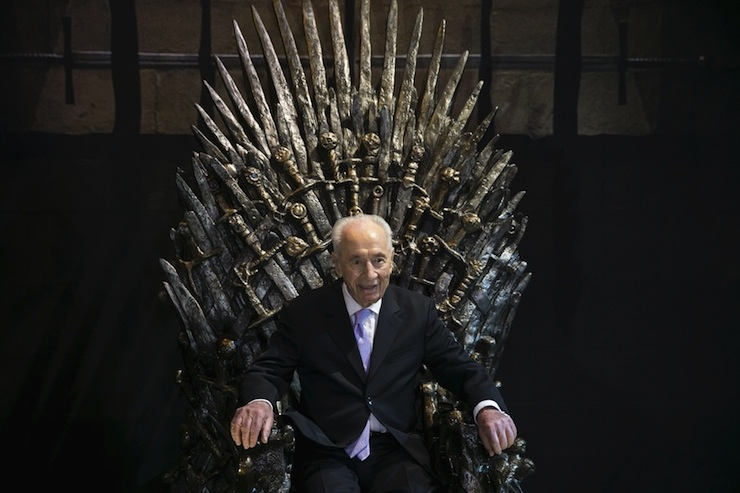 Former Israeli president Peres sits on the Iron Throne as he opens the Game of Throne exhibition in Tel Aviv