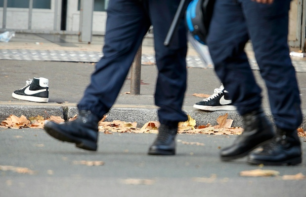 Police pass a pair of abandoned shoes seen left in the street near the Bataclan concert hall the morning after a series of deadly attacks in Paris, November 14, 2015. REUTERS/Charles Platiau